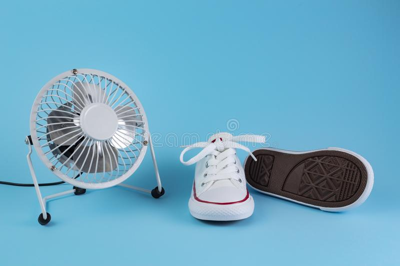 Photo of white electric fan and white sneakers over blue background. royalty free stock images