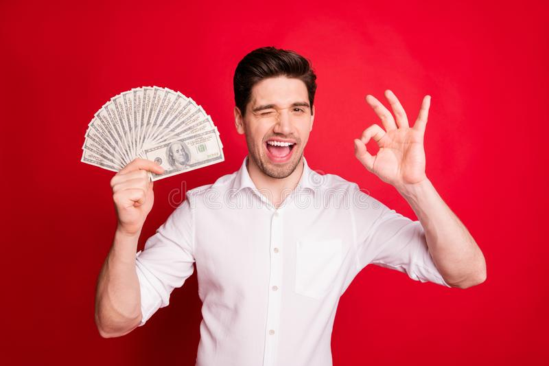 Photo of white handsome blinking winking rich man showing you that everything is ok while isolated with red background. Photo of white handsome blinking, winking stock photos