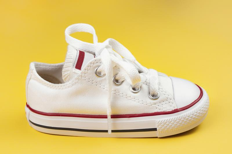 Photo of white sneakers over yellow background. royalty free stock image