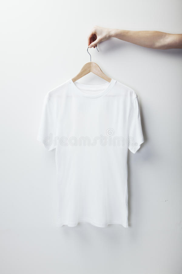 Photo of white tshirt hanging female hand. Vertical royalty free stock photo