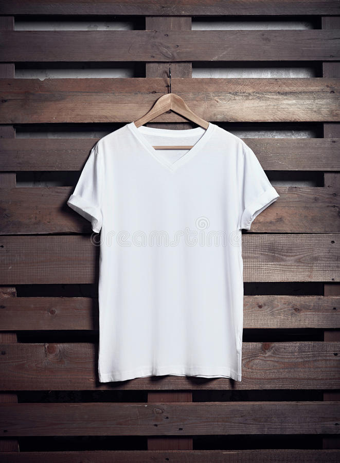 Photo of white tshirt hanging on wood background. Vertical blank mockup royalty free stock photos