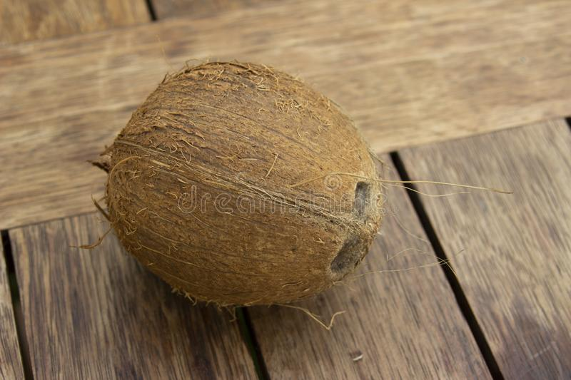 The photo of a whole coconut on the wood table. Vegetarian and healthy food. Cosmetic industry. The photo of a whole coconut on the wood table. Vegetarian and stock photo