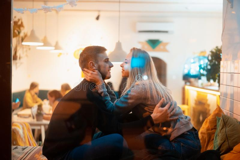 Photo through window. Young couple in cafe with stylish interior royalty free stock images