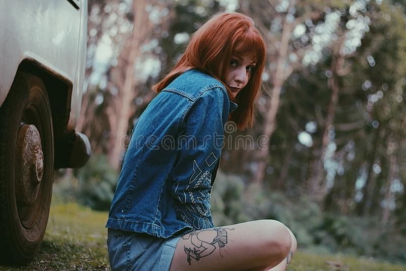 Photo of a Woman in Blue Denim Jacket Sitting Near White Car stock images