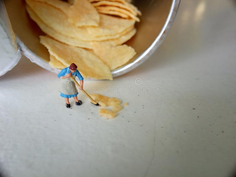 Conceptual, Photo 1 woman cleaning spill of cheese potato chips. Photo 1 woman cleaning spill of cheese potato chips stock images