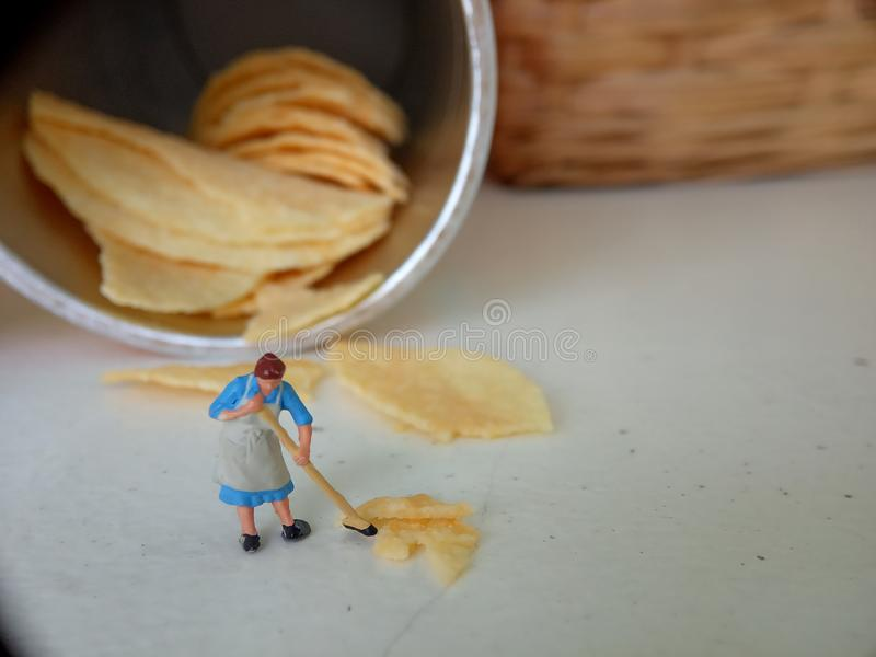 Conceptual, Photo 1 woman cleaning spill of cheese potato chips. Photo 1 woman cleaning spill of cheese potato chips royalty free stock photography