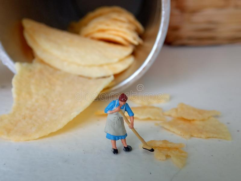 Conceptual, Photo 1 woman cleaning spill of cheese potato chips. Photo 1 woman cleaning spill of cheese potato chips royalty free stock image