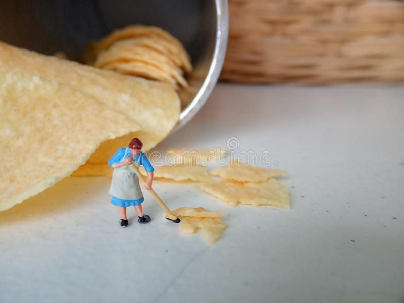 Conceptual, Photo 1 woman cleaning spill of cheese potato chips. Photo 1 woman cleaning spill of cheese potato chips stock photography