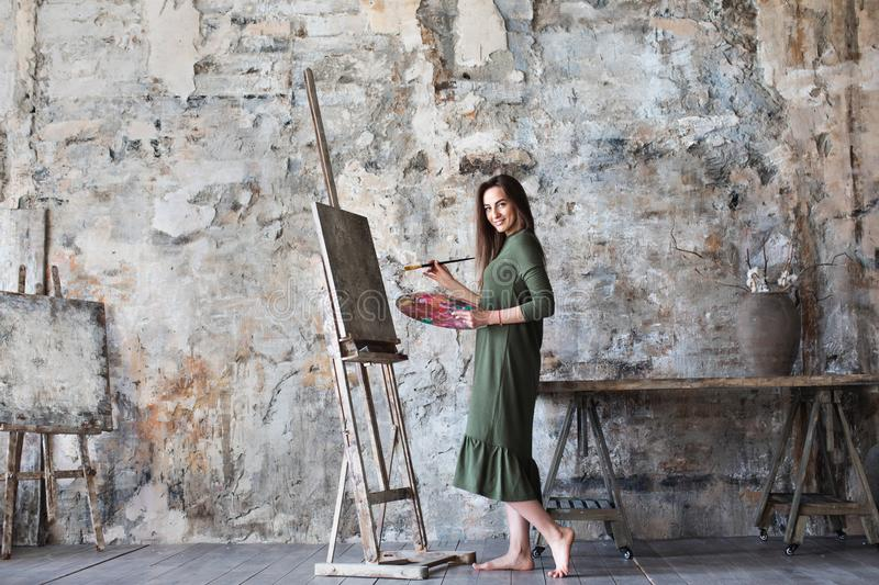 Photo of a woman dressed in a green dress painting in an art studio and smiling. royalty free stock images
