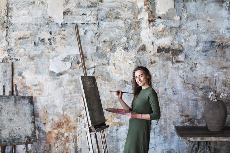 Woman in a green dress painting in an art studio and smiling royalty free stock photo