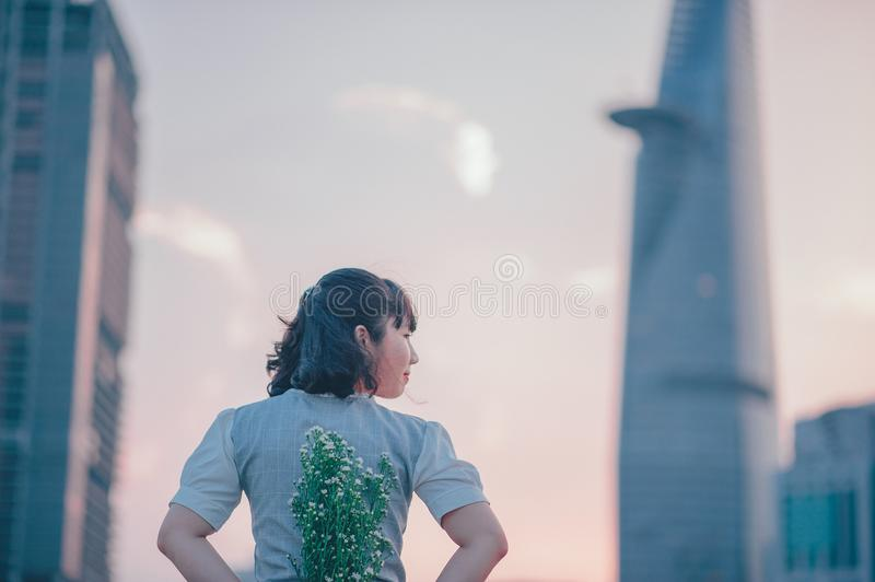 photo of Woman in Gray Top Holding Flowers on Her Back royalty free stock image