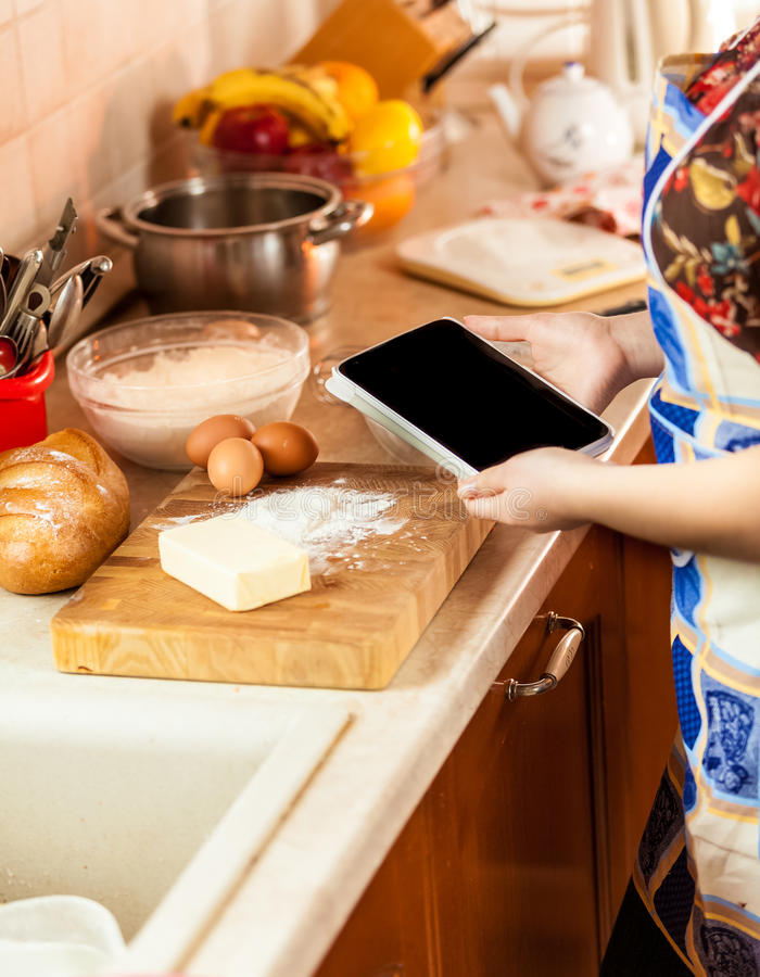 Photo of woman looking recipe on tablet while making dough royalty free stock image
