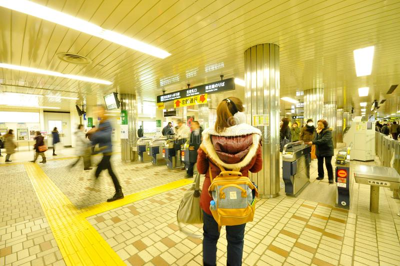 A woman in red sweater is standing alone in subway station with stock photography