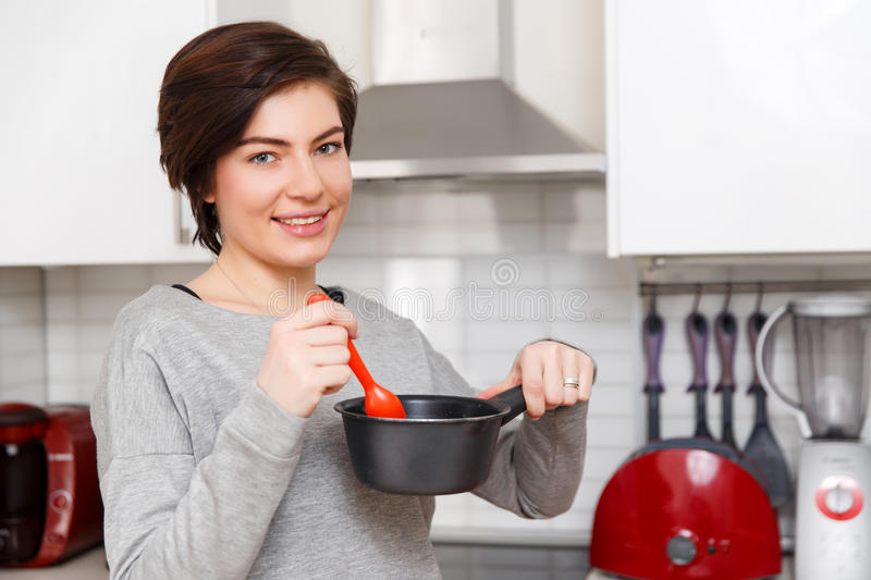 Photo of woman with saucepan. In kitchen stock image