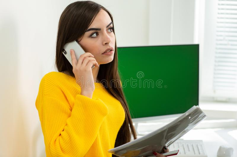 Photo of woman, talking on phone and reading documents in office. Green screen in the background royalty free stock images