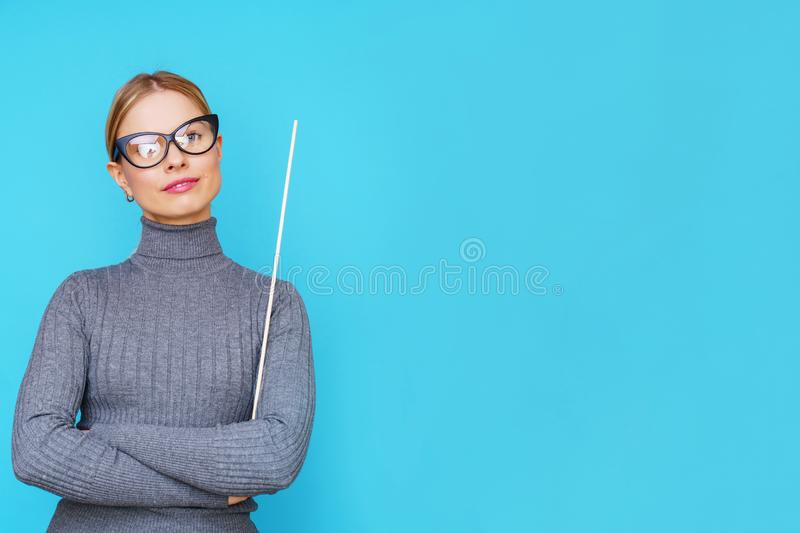 Photo of woman teacher with pointer on empty blue background. royalty free stock photo
