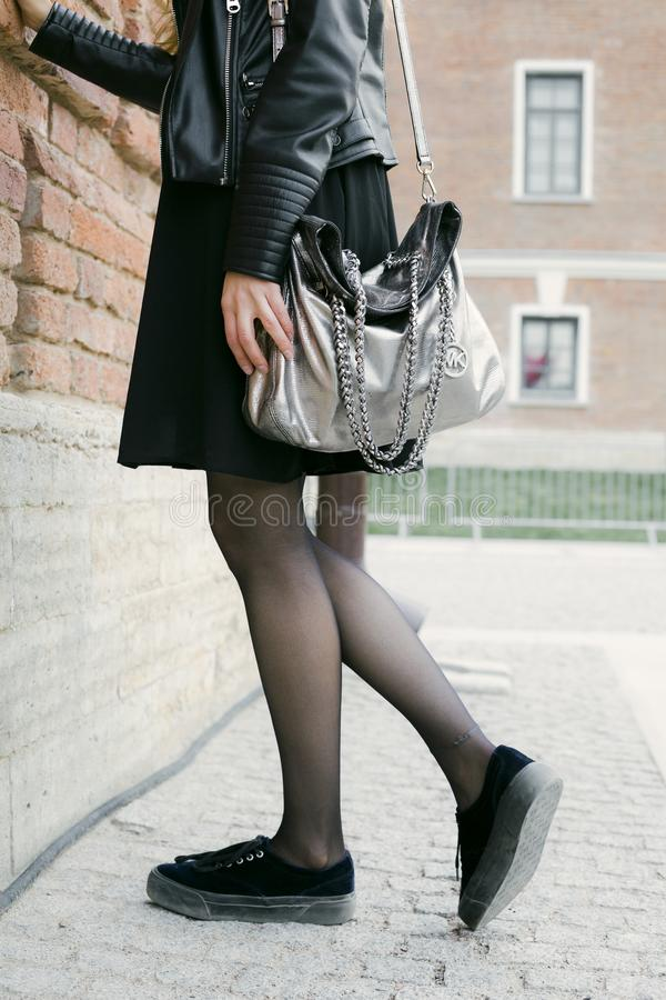 Photo of Woman Wearing Black Leather Zip-up Jacket, Black Mini Skirt, Gray Michael Kors Leather Bag, and Black Low-top Sneakers stock image