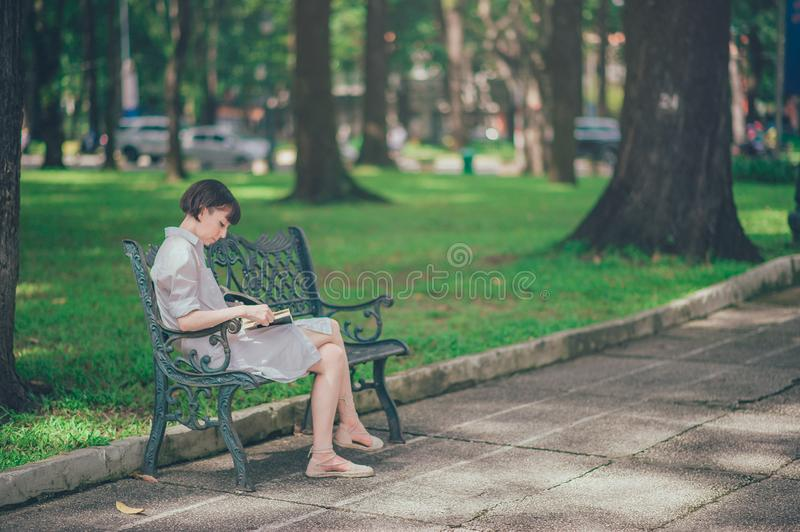 Photo of Woman Wearing Gray Dress Sitting on Bench royalty free stock image