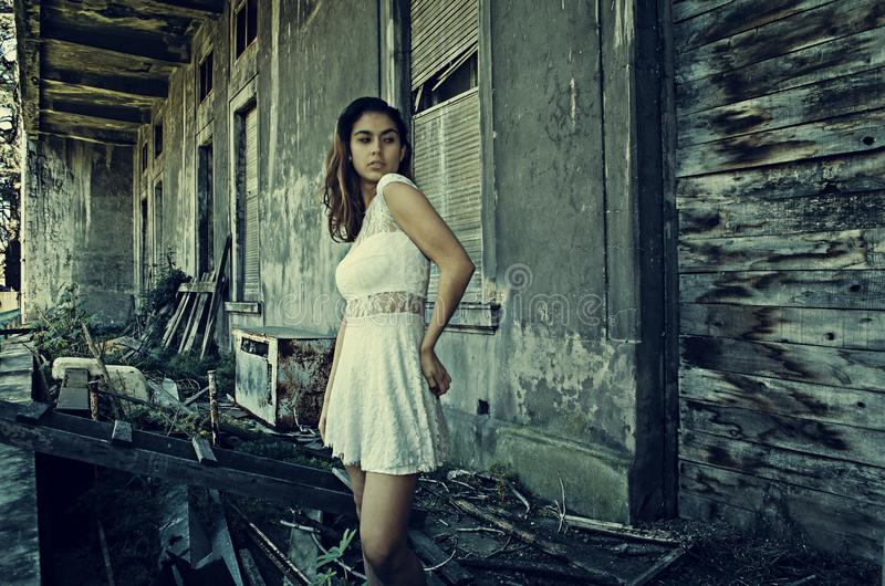 Photo of Woman Wearing White Dress Standing Near Abandoned Building stock photography