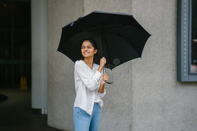 Photo of Woman Wearing White Long-sleeved Shirt and Blue Jeans Holding Black Umbrella stock photo