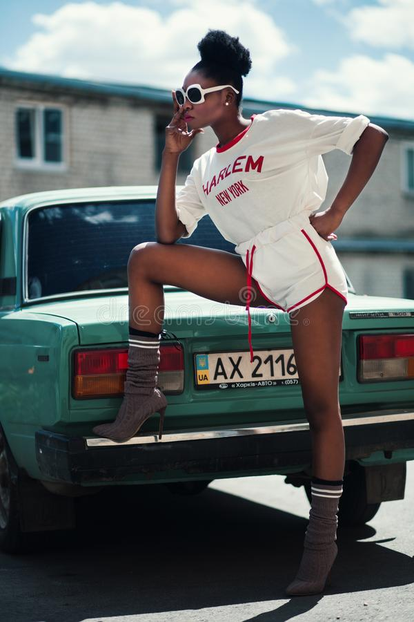 Photo of Woman Wearing White Long-sleeved Shirt and White Dolphin Shorts With Red Trim Standing Near Teal Car stock images