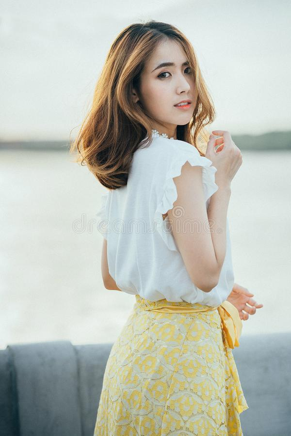 Photo of Woman Wearing White Sleeveless Shirt and Yellow Floral Skirt Near Body of Water royalty free stock photography