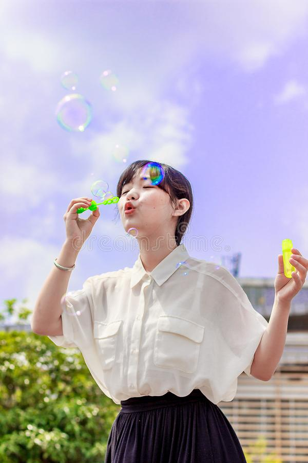 Photo of Woman in White Blouse Playing With Bubbles royalty free stock photo