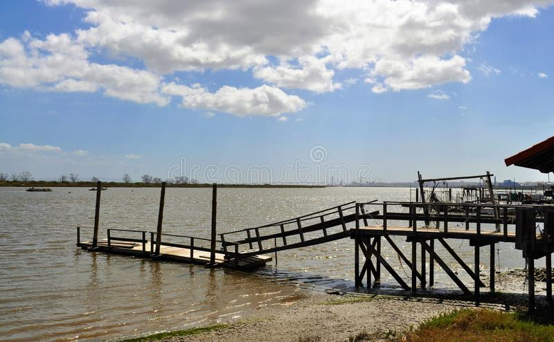 The old fishing harbor under a blue sky. Photo of a wood harbor in Tejo River with high tide and, behing, Lisbon city and Vasco da Gama bridge - Póvoa de Santa royalty free stock image