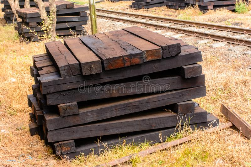 Photo of wooden sleeper, pile up beside railroad stock photos