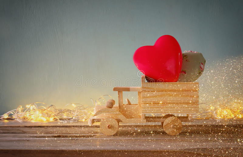 Photo of wooden toy truck with hearts in front of chalkboard. valentine's day celebration concept. vintage filtered stock image