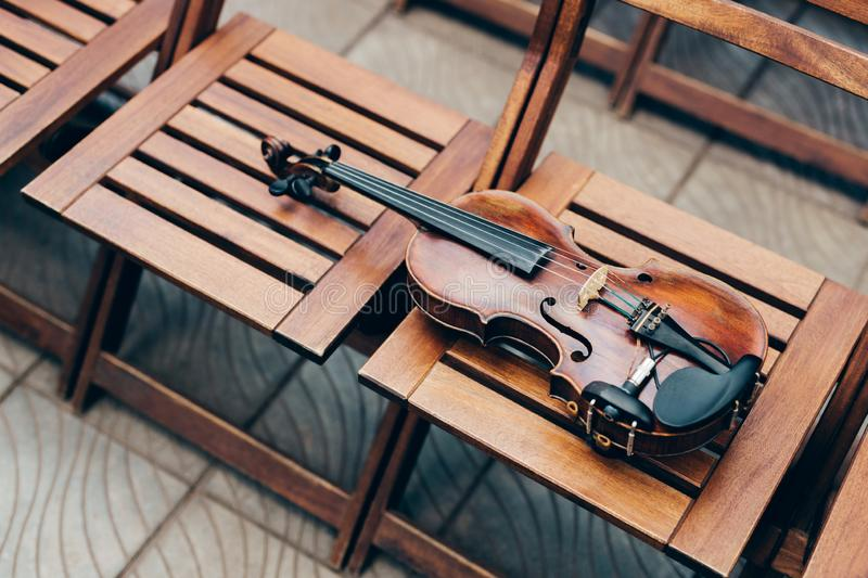 Photo of wooden violin on chairs. Horizontal shot. Live music on special occasion. Outdoor photo. Musical instrument under open royalty free stock image