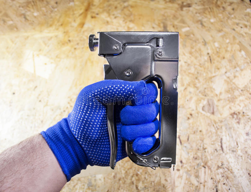 Photo of a worker hand with stapler. Worker hand in blue dotted gloves holding steel industrial stapler on a wooden surface board background royalty free stock photography