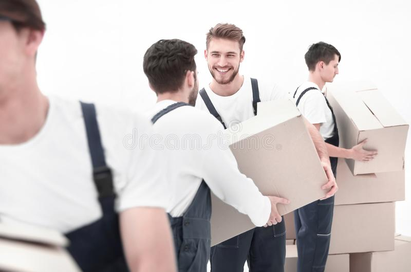 Photo workers pass each other boxes when moving flats. Men delivering box isolated on white royalty free stock photography