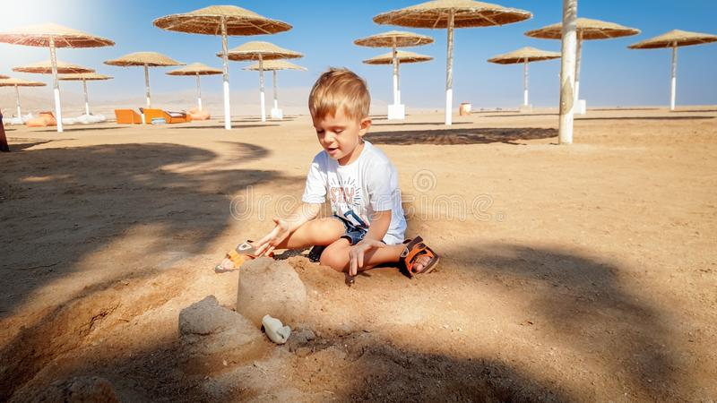 Image of 3 years old little toddler boy sitting on the sea beach and building castle from wet sand stock photos