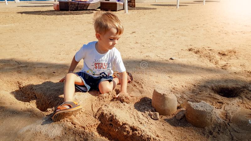 Image of 3 years old little toddler boy sitting on the sea beach and building castle from wet sand stock image