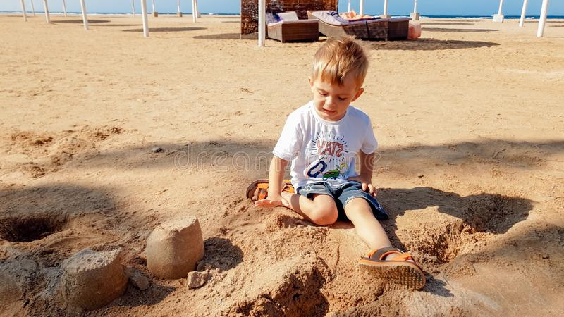 Image of 3 years old little toddler boy sitting on the sea beach and building castle from wet sand royalty free stock photos