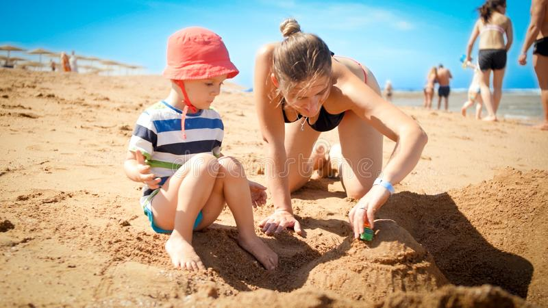 Photo of 3 years old toddler boy building sand castle with young mother the ocean beach. Family relaxing and having fun. On summer holiday vacation stock photography
