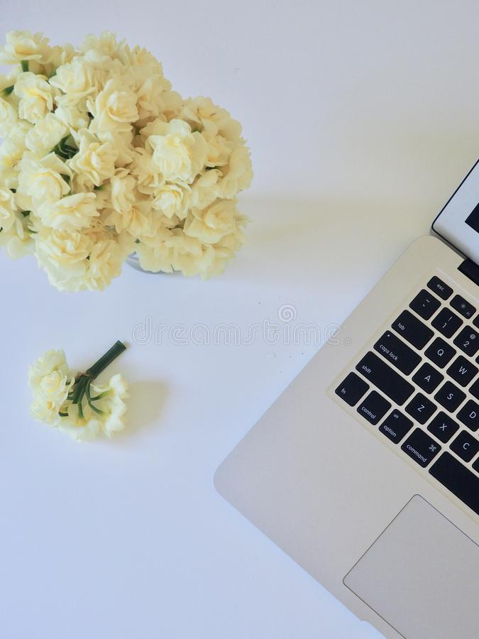 Photo of Yellow Flower Bouquet and White and Black Laptop Computer stock image