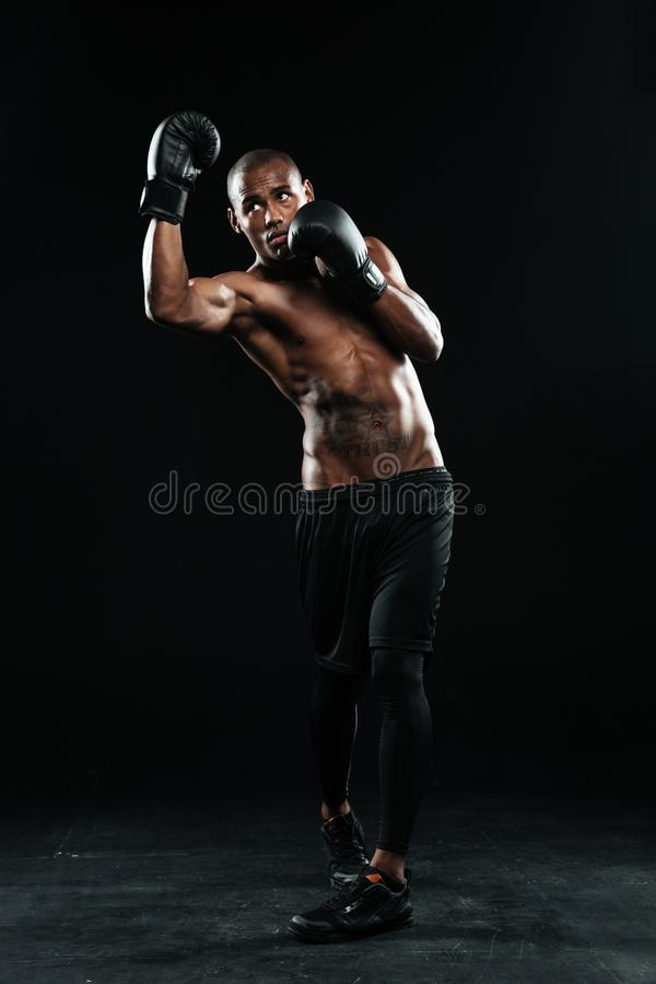 Photo of young afroamerican boxer, standing in protection pose. Photo of young afroamerican boxer in black gloves, standing in protection pose on black royalty free stock photos