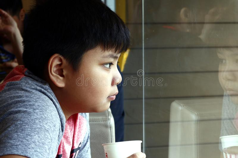 Young Asian boy drink from a paper cup inside a fast food restaurant stock photo