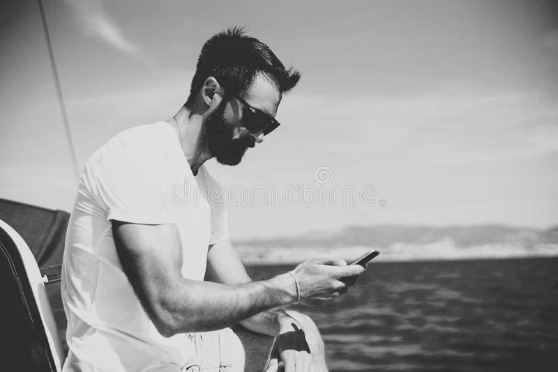 Photo of young bearded man touching screen oF smartphone on the yacht in sunny day. Horizontal mockup, black and white royalty free stock photo