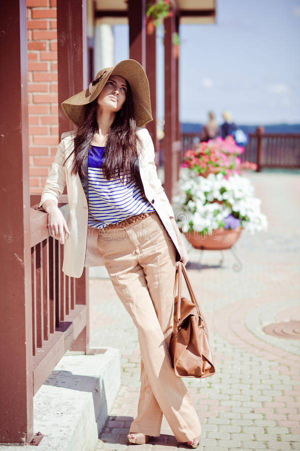 Photo of a young beautiful woman. Brunette fashion fabrics in todays casual elegant hat with a bag royalty free stock photography