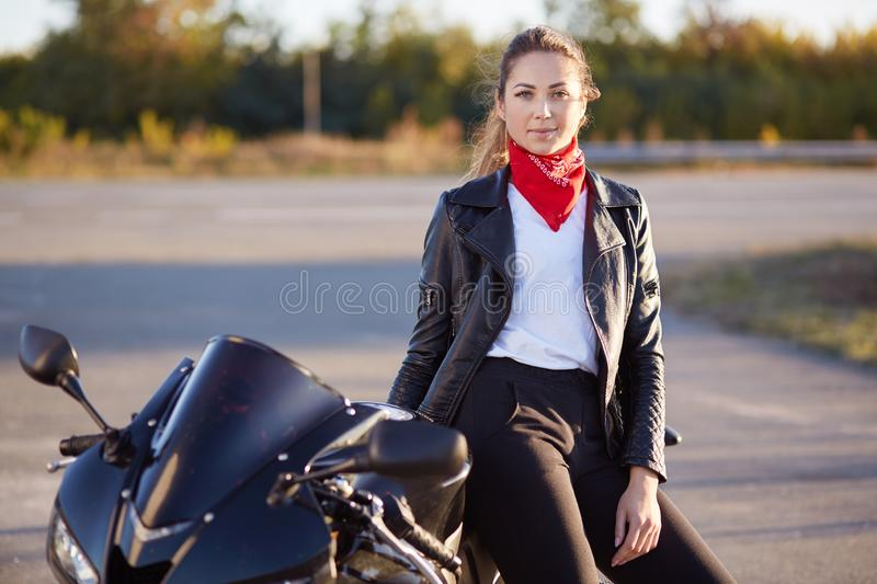 Photo of young beautiful woman stands near her cool motorrbike, wears red bandana, leather jacket, black trousers, white t shirt,. Looking at camera, enjoys royalty free stock images