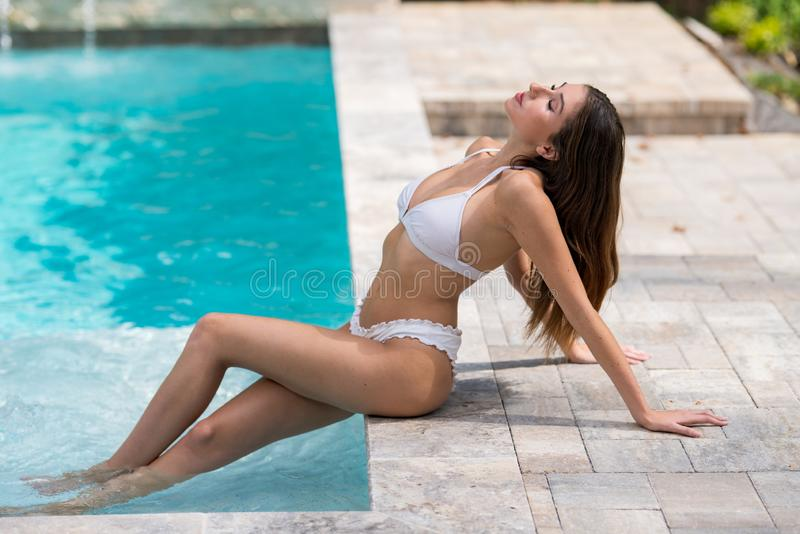 Photo of a young bikini model posing by the pool. Summer vacation theme and healthy lifestyles stock photo