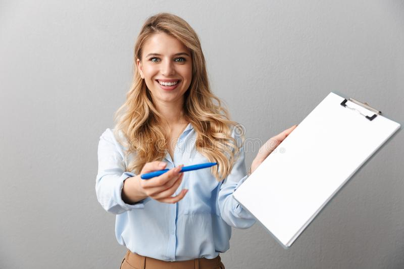 Photo of young blond secretary woman with long curly hair writing down notes in clipboard while working in office stock photos