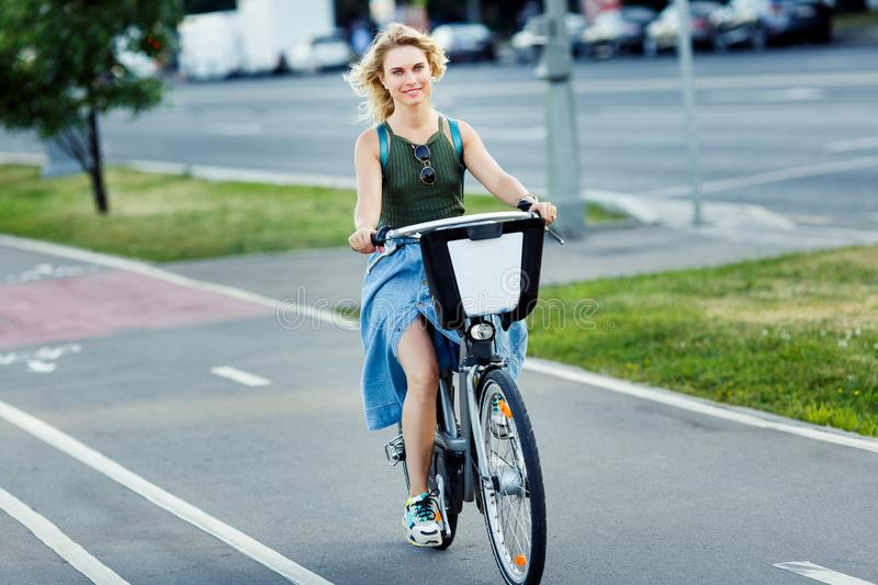 Photo of young blonde in long denim skirt riding bike on road in city stock photo