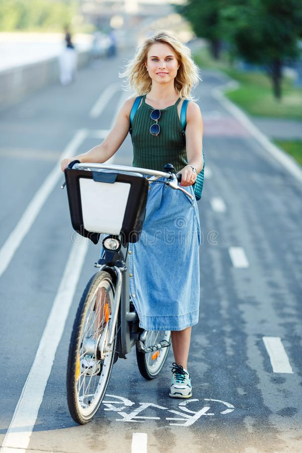 Photo of young blonde in long denim skirt sitting on bike on road in city royalty free stock images