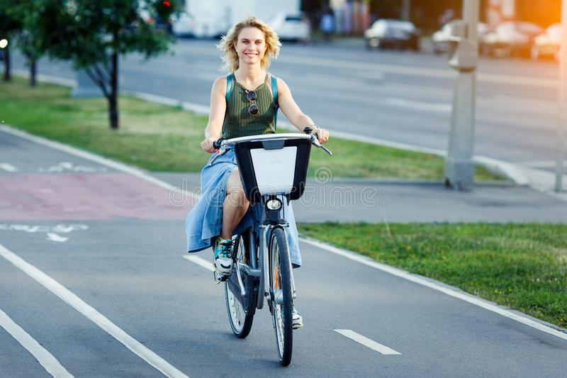Photo of young blonde in long denim skirt sitting on bike on road in city on summer day royalty free stock photo