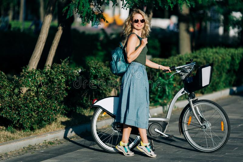 Photo of young blonde in long denim skirt standing next to bike on road next to green bushes in city stock photo