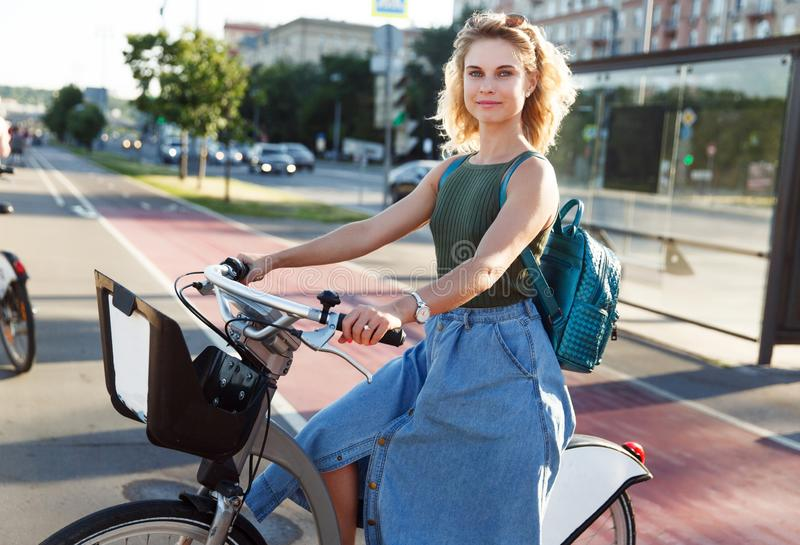 Photo of young blonde sitting on bicycle near bus stop royalty free stock image